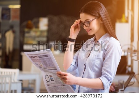 Be informed. Pleasant delighted beautiful woman holding her glasses and reading newspaper while feeling happy