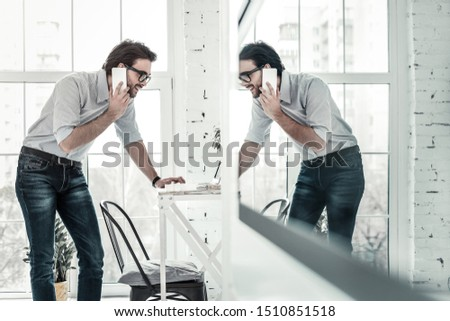 Be positive. Pleased brunette demonstrating his smile while talking per telephone with his interlocutor