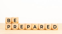 Be prepared phrase in wooden blocks on table. White background. Copy space