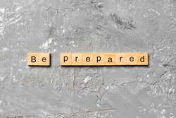 BE PREPARED word written on wood block. BE PREPARED text on cement table for your desing, concept.