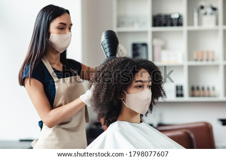 Be safe and beautiful. Hairdresser and customer wearing protective masks at beauty salon, close up Stock photo ©