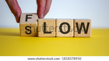 Photo of  Be slow or in the flow. Male hand turns a cube and changes the word 'slow' to 'flow'. Beautiful yellow table, white background, copy space. Business concept.