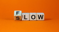 Be slow or in the flow. Turned a cube and changed the word 'slow' to 'flow'. Beautiful orange background, copy space. Business and flow or slow concept.