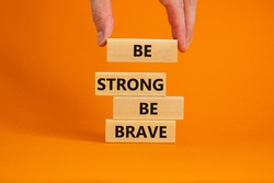Be strong be brave symbol. Wooden blocks with words 'be strong be brave'. Beautiful orange background. Businessman hand. Copy space. Motivational, business and strong brave concept.