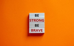 Be strong be brave symbol. Wooden blocks with words 'be strong be brave'. Beautiful orange background. Copy space. Motivational, business and strong brave concept.