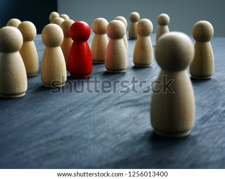 Be Unique, think differently, individuality. Wooden figures and one red figure.