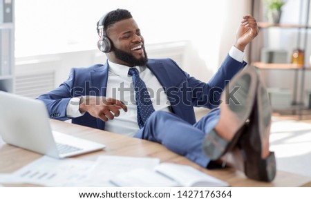 Be whatever you want. Young african worker in suit with legs on the table listening to music and playing on virtual guitar at workplace, free space