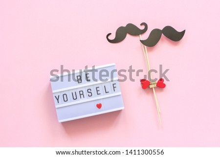 Be yourself Lightbox text, couple paper mustache props on pink background. Concept LGBT, Homosexuality gay love, National Day Against Homophobia or International Gay Day Top view Greeting card.