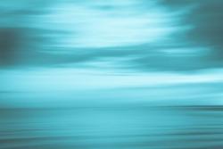 Beach abstract split tone in blue hues St Kilda Beach back-lit by setting sun, Melbourne Australia.
