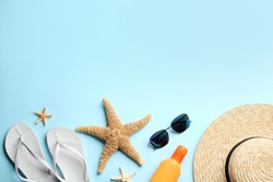 Beach accessories on light blue background, flat lay. Space for text