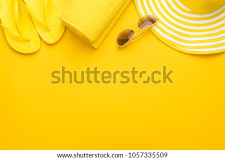 beach accessories on the yellow background - sunglasses, towel. flip-flops and striped hat. summer is coming concept #1057335509