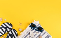 Beach accessories on yellow background. Flip flops,Sun Glasses, towel.Summer vacation concept.Travel mood to the sea.Flat lay.
