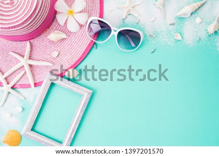 Beach accessories Picture Frame, sunglasses, starfish beach hat and sea shell on bright pastel green background for summer holiday and vacation concept.