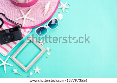 Beach accessories retro film camera, picture frame, sunglasses, starfish, beach hat and sea shell on green background for summer holiday and vacation concept.