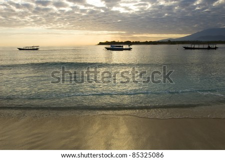 Beach and boats on Trawangan on morning, in Gili islands, near Lombok, Indonesia - stock photo