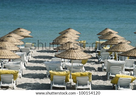 beach and empty lounge chairs by the blue sea
