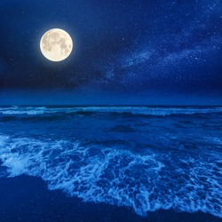 beach and sea on a cloudy night. beautiful view of waves rolling the coast beneath a glowing sky in full moon light