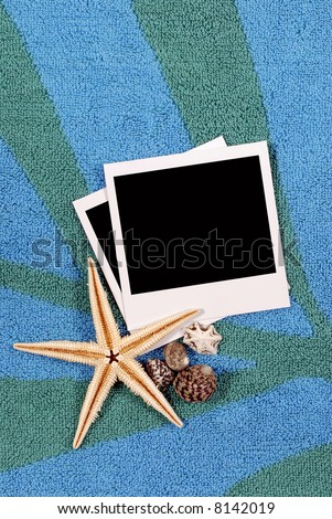 Beach background with beach towel, starfish, shells and blank instant photo prints