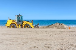 Beach backhoe with pile of sand. Heavy construction equipment vehicle digging sand by the ocean. Orange traffic cone. Clear blue sky, calm water in background. Horizontal photo.