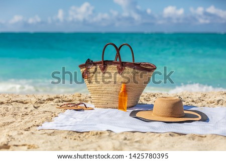 Beach bag on summer vacation background womens purse with travel accessories for sun protection suntan vacations. Sunglasses, tanning oil or sunscreen, hat lying on towel.