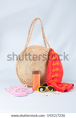 beach bag,towel,sunglasses,flip flops,cream and starfishes on blue background