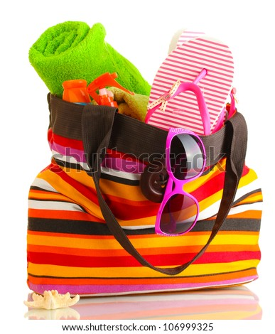 Beach bag with beach accessories, isolated on white - stock photo
