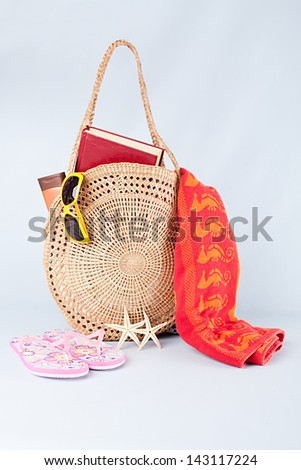 beach bag with full summer stuff on blue background