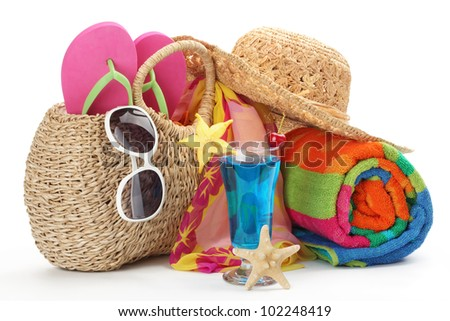 Beach bag with towel,flip flops and sunglasses.