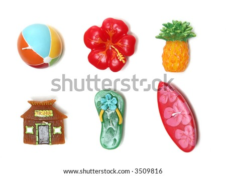 Beach ball, lei, pineapple, sandal, hut, and surfboard candles with a Hawaii theme