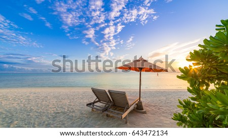 Beach. Beach chairs and umbrella with sunbeam and beautiful moody sky  Tropical holiday banner #643472134
