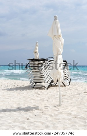 Beach, beautiful weather, sun loungers and umbrellas waiting for tourists in Cancun, Mexico. This is one of the best beaches in the Mexico.