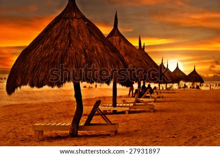 Beach beds and umbrellas at colorful dawn