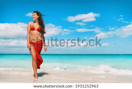 Beach bikini model in red swimsuit and skirt for wellness spa luxury. Hair removal laser treatment for legs and body summer ready vacation Asian woman walking relaxing at Caribbean travel holiday. Foto stock ©