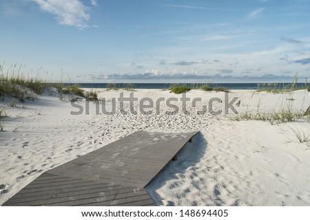 Beach boardwalk footpath meets the sand on beautiful Gulf Coast beach in the early morning.