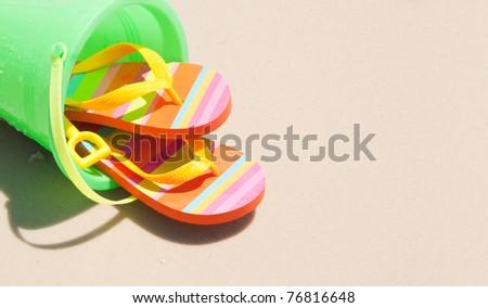 beach bucket and flip flops with copyspace