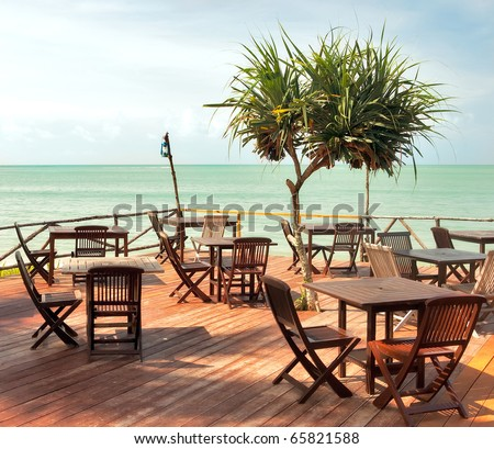 Beach cafe with wooden tables and chairs placed at the sea waterfront