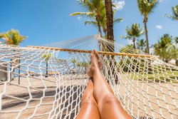 Beach Caribbean travel holiday vacation woman feet selfie lying down relaxing on hammock oustside sunbathing. Girl relaxing taking pov photo of her legs sun tanning in tropical summer destination.