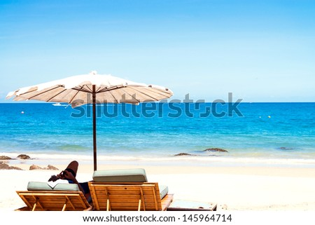 Beach chair and umbrella on sand beach.