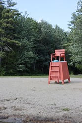 beach chair life guard stand on lake beach ocean in sand red wooden tall guard chairs with green trees behind in summer safely lifeguard station stand wood chair with ladder