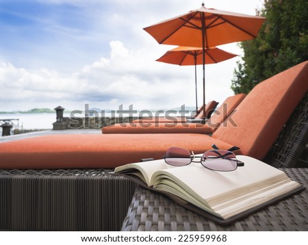 Beach chair Summer holiday vacation with book and eyeglasses