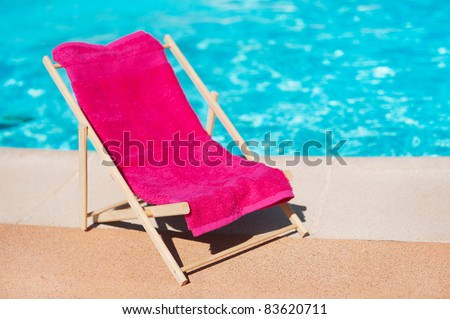 Beach chair with towel near the swimming pool