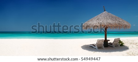 Beach Chairs and Umbrella on a beautiful island, panoramic view with much copy space