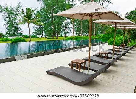 Beach chairs and umbrella side swimming pool - stock photo