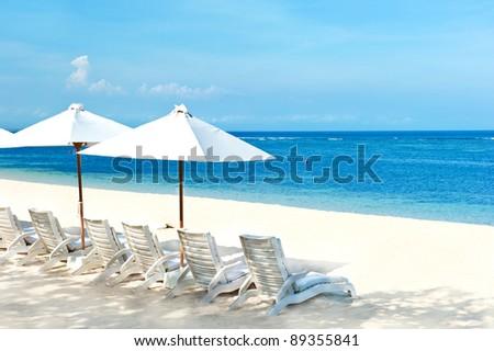 beach chairs and umbrellas on beautiful tropical sand beach