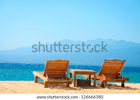 Beach chairs on perfect tropical yellow sand beach with blue sea and island on background, Gili, Bali, Indonesia