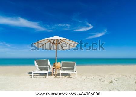 Beach chairs on the white sand beach with cloudy blue sky #464906000