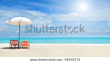 Beach chairs on the white sand beach with cloudy blue sky and sun #98418176