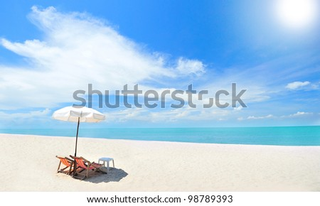 Beach chairs on the white sand beach with cloudy sky and sun