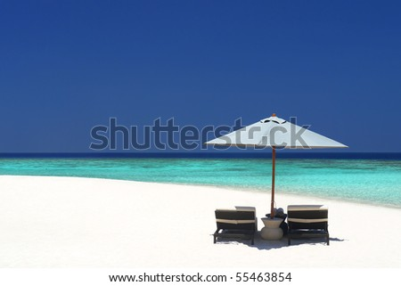 Beach chairs under an umbrella on a quiet stretch of pristine beach