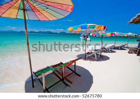 Beach chairs with umbrella along beach front
